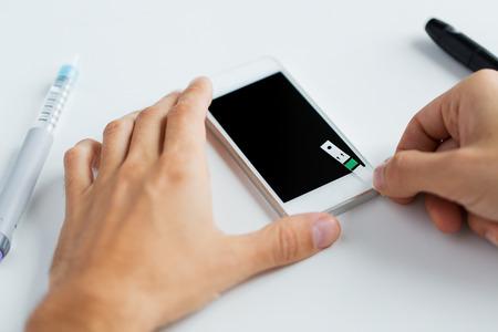 diabetes: la medicina, la diabetes, la glucemia, la salud y las personas concepto - cerca del hombre con el teléfono inteligente revisar el nivel de azúcar en la sangre por glucómetro en casa