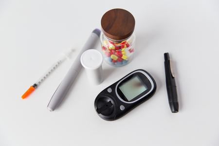 medicine, diabetes and health care concept - close up of glucometer, insulin pen, drug pills and other diabetic tools on table