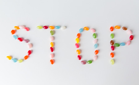 carbohydrates: food, sweets, confectionery and unhealthy eating concept - close up of colorful jelly beans candies on table