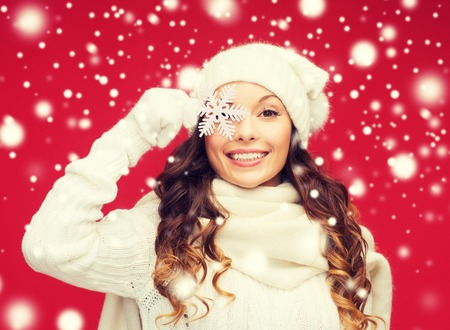 cold woman: winter, people, happiness concept - woman in hat, muffler and gloves with big snowflake Stock Photo