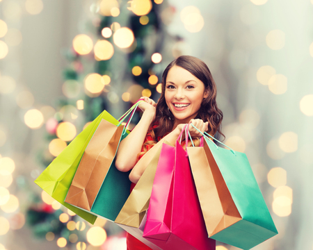 fashion bag: sale, gifts, holidays and people concept - smiling woman with colorful shopping bags over living room and christmas tree background