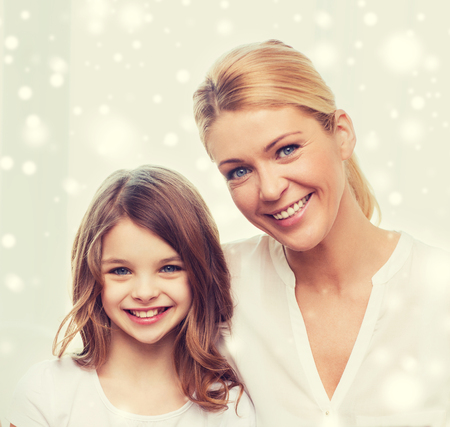 childhood: family, childhood, motherhood, people and happiness concept - smiling mother and little girl over snowflakes background