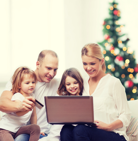family, holidays, shopping, technology and people - happy family with laptop computer and credit card over living room and christmas tree background