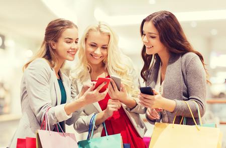 prodej, konzumerismus, technologie a lidé koncept - šťastné mladé ženy s chytrými telefony a nákupními taškami v obchoďáku