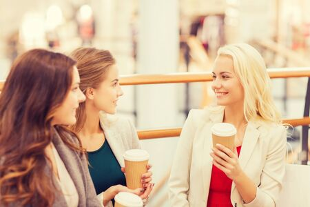 3 people: sale, consumerism and people concept - happy young women with shopping bags and coffee paper cups in mall Stock Photo
