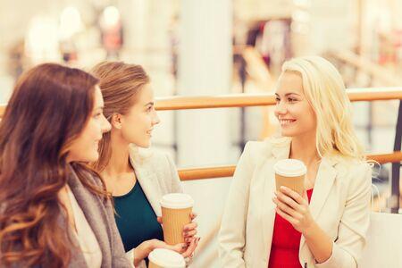 mujer elegante: venta, el consumismo y el concepto de la gente - las mujeres jóvenes felices con bolsas de la compra y vasos de papel café en centro comercial