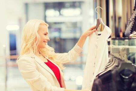 consumerism: sale, consumerism, shopping and people concept - happy young woman choosing clothes in mall