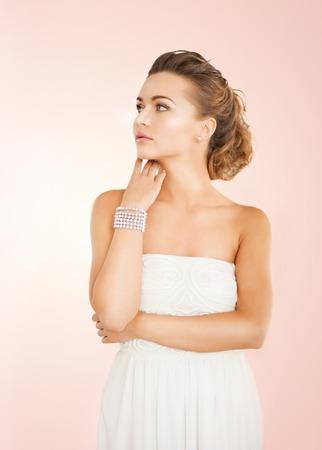 bangles hand: beautiful bride wearing pearl earrings and bracelet