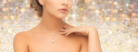 people, jewelry, luxury, holidays and glamour concept - woman wearing shiny diamond pendant over golden lights background Stock Photo