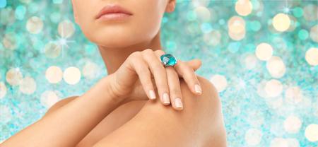 la gente, la joyería, el lujo y el glamour concepto - cerca de la mano de la mujer y el anillo con la gema preciosa sobre luces azul de fondo