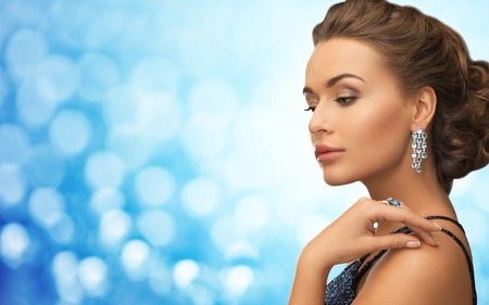 diamond jewelry: people, holidays, jewelry, luxury and glamour concept - beautiful woman with beautiful diamond earrings over blue lights background