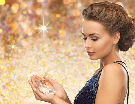 diamante: las personas, las vacaciones y el concepto de glamour - mujer sonriente en traje de noche con diamantes de cristal sobre fondo de oro de las luces Foto de archivo