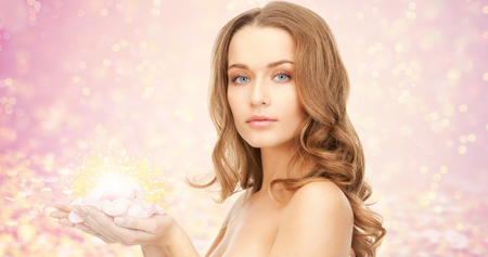 beauty, people, holidays, skin and body care concept - beautiful young woman with rose flower petals and bare shoulders over pink lights background