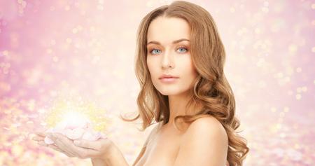 piel: la belleza, la gente, las vacaciones, la piel y el concepto de cuidado del cuerpo - mujer joven hermosa con p�talos de flores rosas y los hombros al descubierto m�s de luces de color rosa de fondo