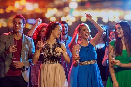 bebiendo vino: fiesta, días de fiesta, celebración, vida nocturna y concepto de la gente - amigos felices con vasos de champán baile no alcohólica en discoteca en discoteca