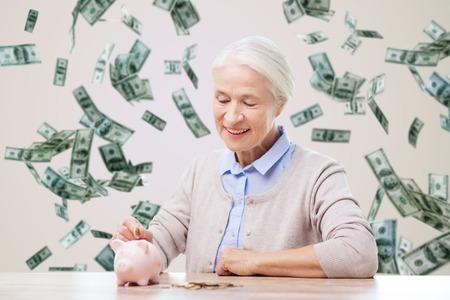 貯蓄、財政、年金保険、退職および人々 のコンセプト - 笑顔お金雨背景で貯金箱にコインを入れ年配の女性