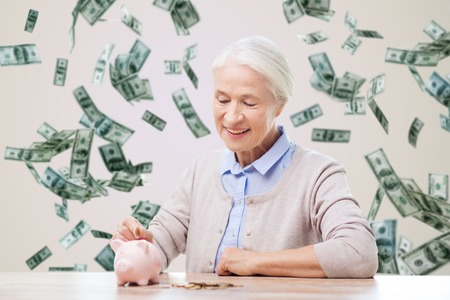 savings, finances, annuity insurance, retirement and people concept - smiling senior woman putting coins into piggy bank over money rain background
