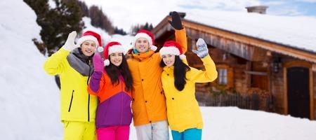 personas saludando: vacaciones de invierno, navidad, la amistad y el concepto de la gente - amigos felices en Santa sombreros y trajes de esquí que agitan las manos al aire libre sobre fondo de madera casa de campo y la nieve