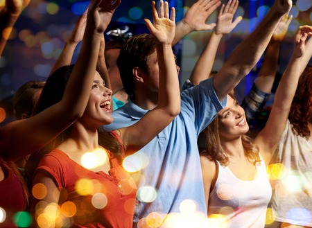 arms raised: party, holidays, celebration, nightlife and people concept - smiling friends waving hands at concert in club