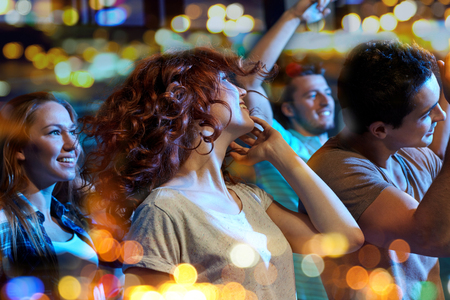 discotheque: party, holidays, nightlife and people concept - happy friends dancing at night club Stock Photo