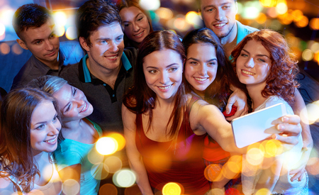 friends happy: party, technology, nightlife and people concept - smiling friends with smartphone taking selfie in club