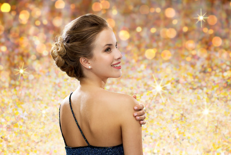 glamour woman: people, holidays and glamour concept - smiling woman in evening dress from back over golden lights background
