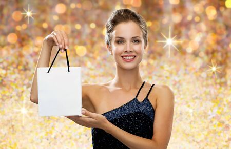 holydays: shopping, luxury, advertisement, people and sale concept - smiling woman with white blank shopping bag over golden holydays lights background