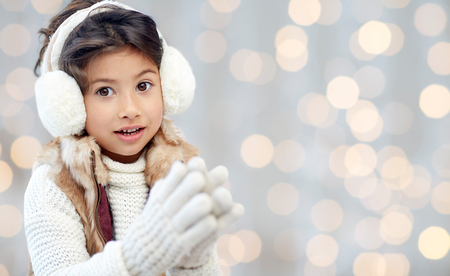 preteen asian: winter, people, christmas happiness concept - happy little girl wearing earmuffs and gloves over holidays lights background