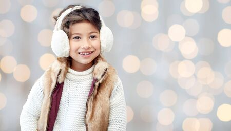 asian style: winter, people, christmas, fashion and childhood concept - happy little girl wearing earmuffs and gloves over holidays lights background