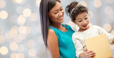 latin family: holidays, birthday, family, childhood and people concept - happy mother and little girl with gift over lights background Stock Photo