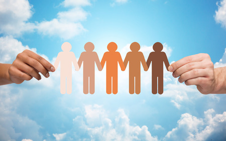 community, unity, population, race and humanity concept - multiracial couple hands holding chain of paper people pictogram over blue sky and clouds background