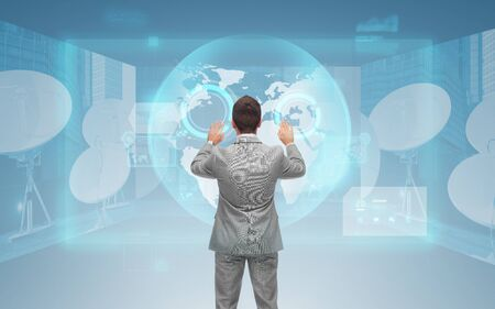 network concept: business, people, global network and technology concept - businessman touching virtual screen with world map and satellite antennas over blue background from back