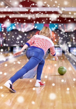 entertainment concept: people, leisure, sport and entertainment concept - happy young woman throwing ball in bowling club at winter season Stock Photo