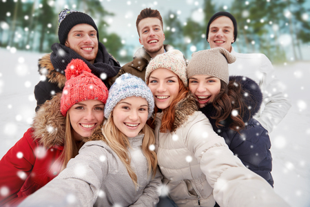 winter fashion: winter, technology, friendship and people concept - group of smiling men and women taking selfie outdoors