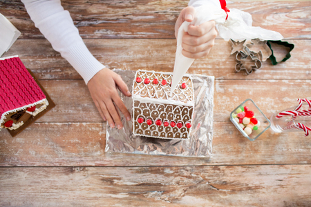 making up: cooking, people, christmas and decoration concept - close up of happy woman making gingerbread houses at home