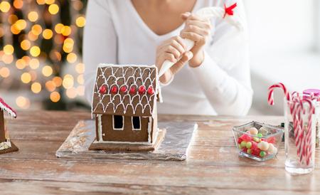 料理、人、クリスマスの装飾の概念 - ジンジャーブレッド家自宅を作る幸せな女のクローズ アップ