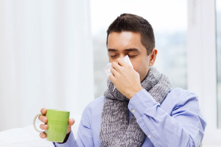 cold virus: healthcare, flu, people, rhinitis and medicine concept - ill man blowing his nose with paper napkin and drinking tea at home