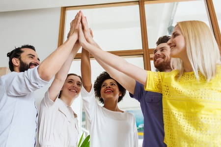 trabajo en equipo: negocio, el arranque, el gesto, la gente y el trabajo en equipo - concepto de equipo creativo feliz haciendo chocar los cinco en la oficina
