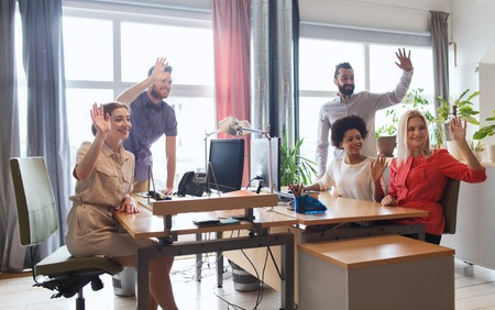waving: business, startup and office concept - happy creative team waving hands in office