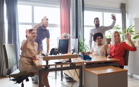 personas saludando: negocio, puesta en marcha y el concepto de oficina - equipo creativo feliz agitando las manos en la oficina Foto de archivo