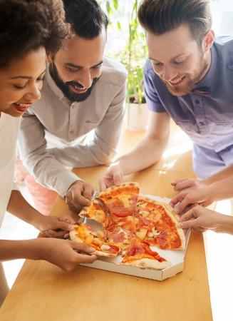 to lunch: negocio, la comida, el almuerzo y la gente concepto - equipo de negocios feliz comiendo pizza en la oficina Foto de archivo
