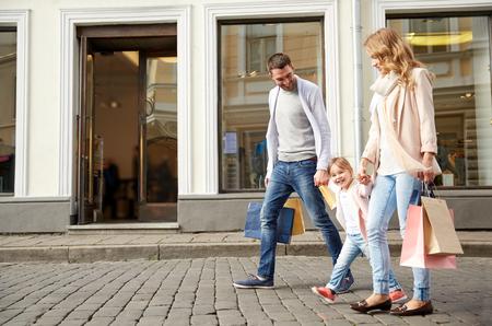 pessoas: venda, o consumismo e as pessoas conceito - família feliz com criança pequena e sacos de compra na cidade
