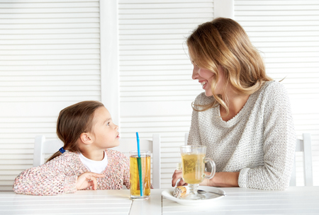 a little dinner: family, parenthood, communication and people concept - happy mother and little girl having dinner and talking at restaurant or cafe