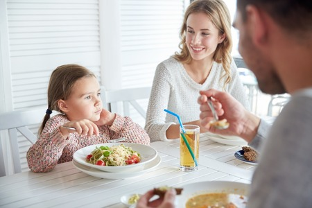 family, parenthood, food and people concept - happy mother, father and little girl eating pasta and soup for dinner at restaurant or cafe