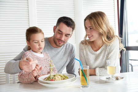 family, parenthood, food and people concept - happy mother, father and little girl eating pasta for dinner at restaurant or cafe Stockfoto