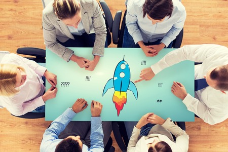 business, people, startup, development and team work concept - close up of creative team sitting at table and pointing finger to rocket icon in office Stock Photo