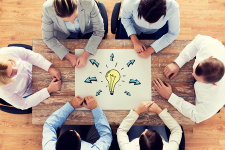 business, people, inspiration and team work concept - close up of business group sitting at table with bulb doodle on paper sheet in office Banco de Imagens - 48791341