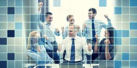 team hands: business, people, technology, gesture and teamwork concept - smiling business team raising hands and celebrating victory in office over blue squared grid background