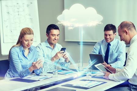 tecnologia: negócio, pessoas, computação em nuvem e conceito da tecnologia - sorrindo equipe do negócio com smartphones, computadores tablet pc que trabalha no escritório