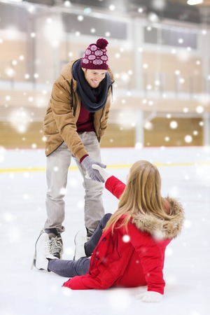 iceskates: people, friendship, sport and leisure concept - smiling man helping women to rise up on skating rink